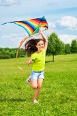 stock photo of kites  - Happy little girl with kite running in the park with kite with smile and long hairs waiving on the wind - JPG