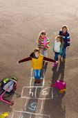 picture of hopscotch  - Boy jumping on hopscotch game with friends boys an girls wearing autumn clothes standing by with school bags laying near - JPG