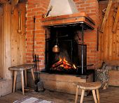 stock photo of chalet interior  - Wood fire in an old style wooden log cabin - JPG