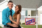 Happy young couple in front of newly sold home