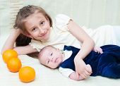 pic of emo-boy  - Older sister hugging baby lying on the bed with oranges - JPG
