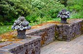 picture of garden sculpture  - Two flower planter sculptures on brick garden wall - JPG