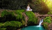 stock photo of padmasana  - Woman practices yoga in nature the waterfall - JPG