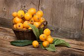 image of loquat  - loquats on a wicker basket on wooden background - JPG