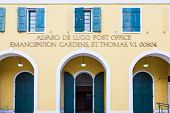 stock photo of old post office  - Old yellow plaster post office in St Thomas with blue shutters on doors and windows - JPG