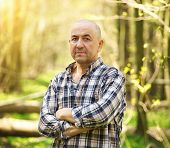 image of tatar  - Middle aged smiling tatar man in the summer forest - JPG