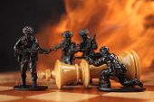 stock photo of killing  - Toy soldiers kill chess King in fire.