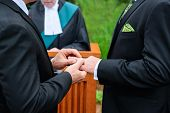 foto of gay wedding  - A man putting a ring on another man