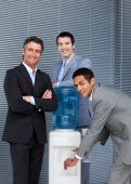 Portrait Of A Business Team Filling Cup From Water Cooler