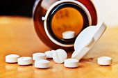 foto of pharmaceutical company  - White Pills Spilling out of Pill Bottle - JPG