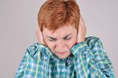 stock photo of frown  - Frowning woman with closed eyes bending her head and covering the ears with hands because of loud noise - JPG