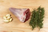 pic of lamb shanks  - Raw lamb shanks on a board with garlic and rosemary - JPG