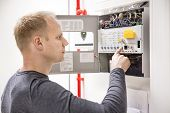 stock photo of engineer  - IT engineer or technician looking at alarm panel for aspirating fire detection system in datacenter - JPG