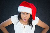 picture of bitchy  - Closeup portrait of unhappy pissed off christmas woman with red hatsticking tongue out disgusted negative human facial expression isolated on grey black background - JPG