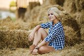 picture of cowgirl  - Beautiful blonde cowgirl posing for a photograph while sitting on hay on a hot summer day in the countryside - JPG