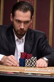 image of shiting  - Handsome  confident man   in casino staking  up red blue and shite chips in piles   looking at  chips   sitting at table with  chips and cards waist up selective focus