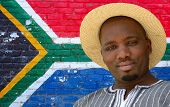 foto of mans-best-friend  - Head portrait of a black man with friendly smiling facial expression on South African flag wall background. ** Note: Visible grain at 100%, best at smaller sizes - JPG