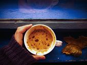 image of hot-weather  - Hand in winter sweater holding a cup of coffee near the window - JPG