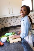 stock photo of diners  - cheerful black woman cooking diner in kitchen - JPG