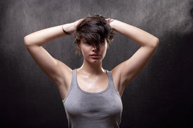 stock photo of strip tease  - Wet young woman with a gray top - JPG