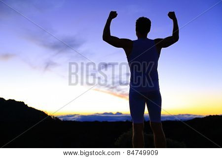 Strength - strong success fitness man flexing muscles showing power pose outside in silhouette at ni