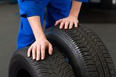 pic of garage  - Mechanic rolling a tire wheel at the repair garage - JPG