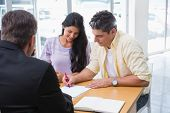 stock photo of showrooms  - Smiling couple signing a contract at new car showroom - JPG