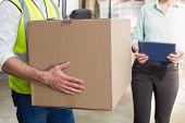 image of warehouse  - Close up of a warehouse worker carrying box in a large warehouse - JPG