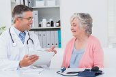 foto of prescription  - Happy male doctor explaining prescriptions to senior patient in clinic - JPG