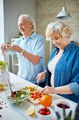 stock photo of wifes  - Senior husband and wife cooking together - JPG