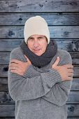picture of shivering  - Casual man shivering in warm clothing against wooden background in blue - JPG