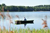 picture of canoe boat man  - fisherman in boat in summer day - JPG