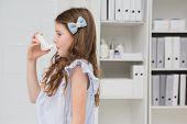 picture of breath taking  - Little girl taking inhaler in medical office - JPG