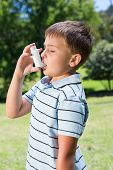 foto of inhalant  - Little boy using his inhaler on a sunny day - JPG
