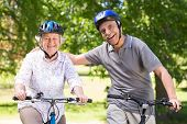 stock photo of exercise bike  - Happy senior couple on their bike on a sunny day - JPG