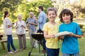 image of extended family  - Extended family having a barbecue on a sunny day - JPG