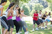 stock photo of tug-of-war  - Fitness group playing tug of war on a sunny day - JPG
