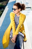 picture of bench  - Young woman in yellow sweater with yellow phone sitting on the bench in the city - JPG