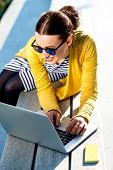 picture of work bench  - Young woman in yellow sweater working with laptop and phone on the bench in the city - JPG