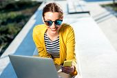 foto of work bench  - Young woman in yellow sweater working with laptop and phone on the bench in the city - JPG