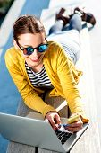 image of work bench  - Young woman in yellow sweater working with laptop and phone on the bench in the city - JPG
