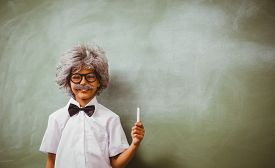 stock photo of half-dressed  - Portrait of little boy dressed as senior teacher in front of blackboard - JPG