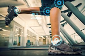 picture of slender  - Fit woman running on the treadmill against fitness interface - JPG