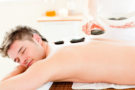 foto of stone-therapy  - Handsome Young Man Receiving A Back Massage With Hot Stone - JPG