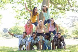 stock photo of human pyramid  - Happy friends in the park making human pyramid on a sunny day - JPG