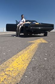 image of muscle-car  - Young handsome man with muscle car outdoors on tarmac - JPG