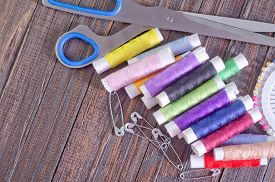 picture of rayon  - color threads and scissors on the wooden table - JPG