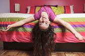 stock photo of upside  - A Young beautiful girl in bedroom upside down - JPG