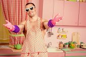 stock photo of apron  - Handsome muscular man in an apron cooking in the pink kitchen - JPG