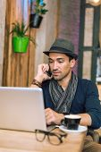 image of internet-cafe  - Fashionable and stylish young man talking on the phone relaxing with coffee music and internet browsing at the cafe bar - JPG